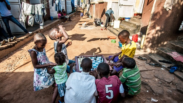 Children gather to watch a chess match after school in Katwe, where much of the upcoming movie was filmed [Aurelie Marrier d'Unienville/Al Jazeera]